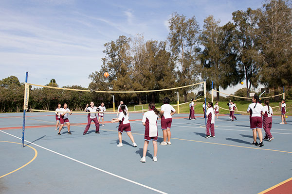 Students at Mary MacKillop Catholic College Wakeley playing game on volleyball court