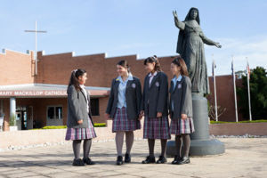 Four students talking in front of Mary MacKillop statue at Mary MacKillop Catholic College Wakeley
