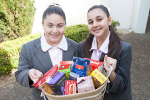 Students at Mary MacKillop Catholic College Wakeley holding basket of food for donation