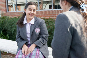 Two Mary MacKillop Catholic College Wakeley students chatting in school grounds